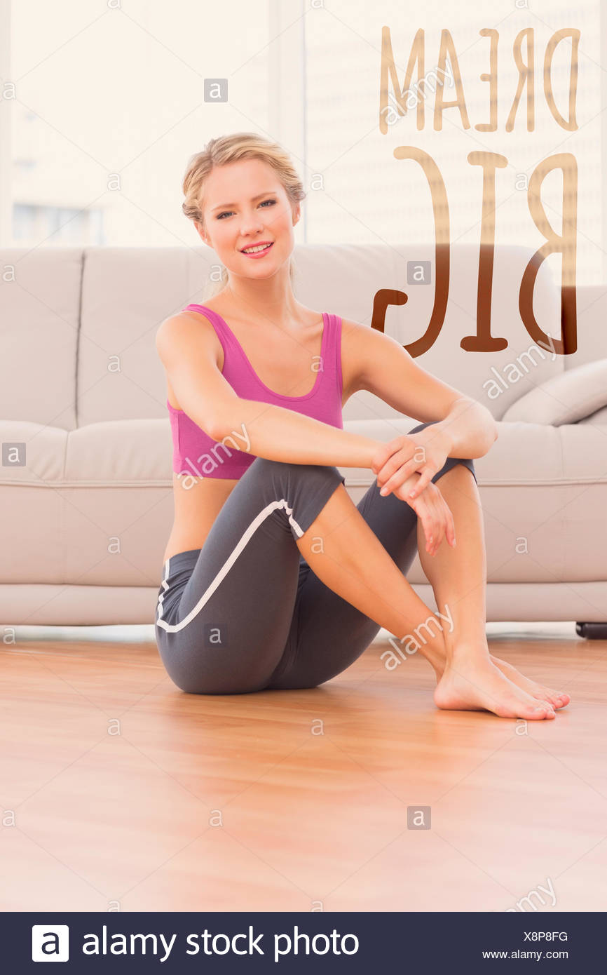 Composite image of athletic blonde sitting on floor smiling at camera - Stock Image