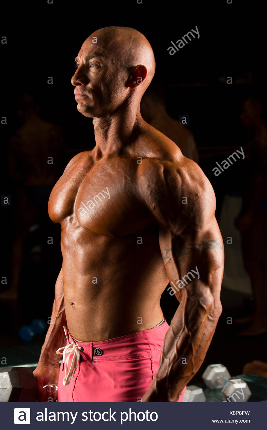 Profile of serious bodybuilder lifting barbell weights - Stock Image