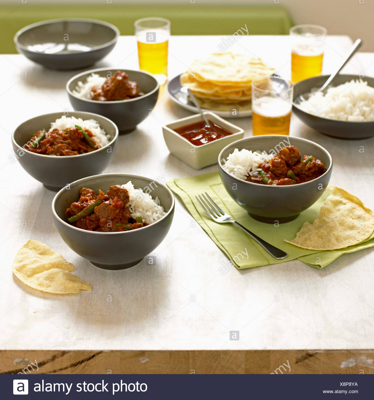 Aromatic beef curry with ginger, okra and tomatoes, served with rice - Stock Image