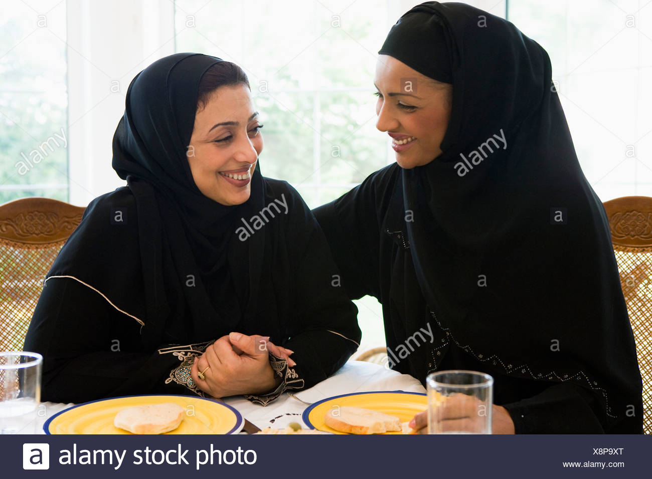 Two women sitting at dinner table smiling (high key) - Stock Image