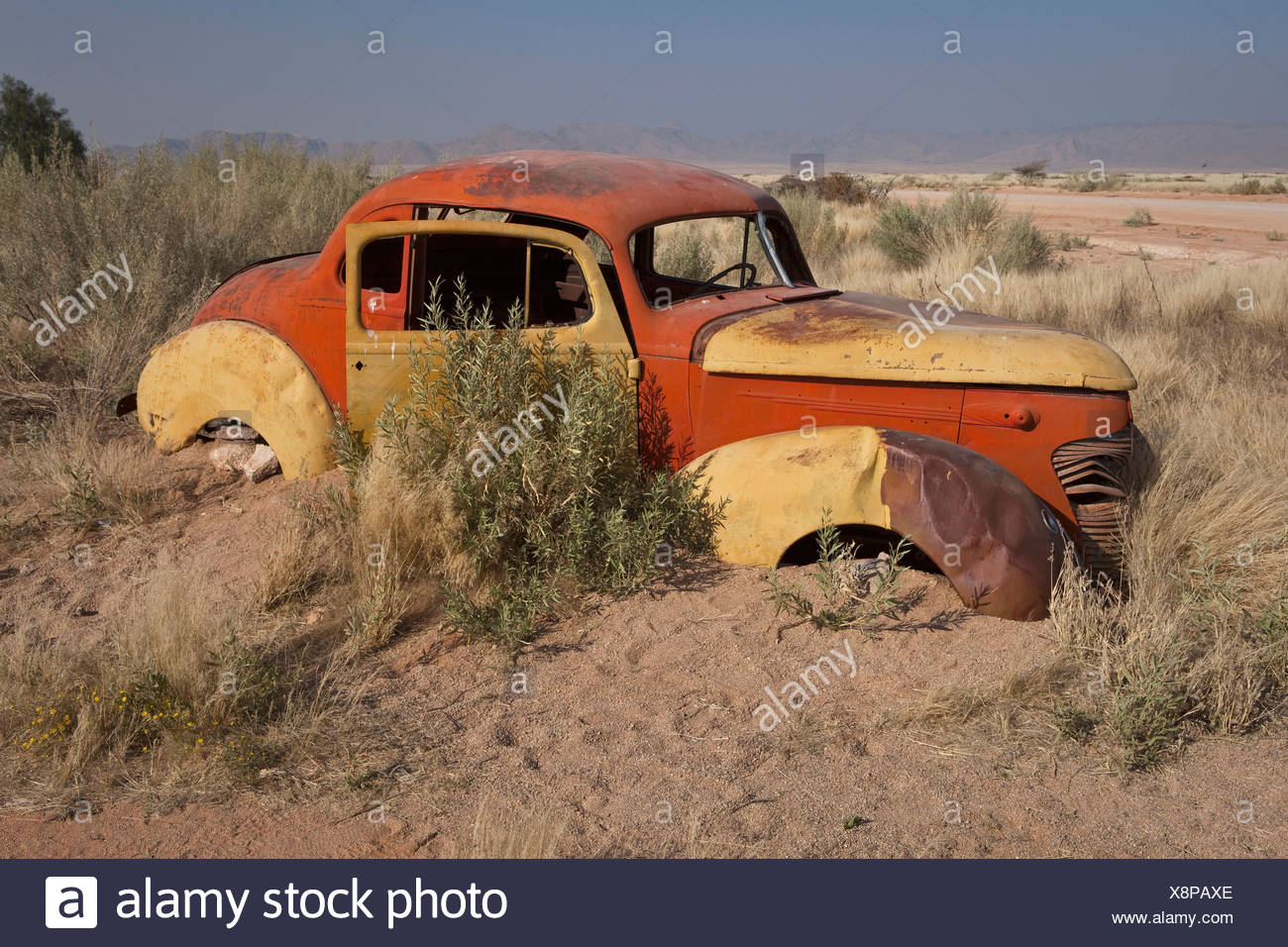 Rusting car submerged in sand - Stock Image