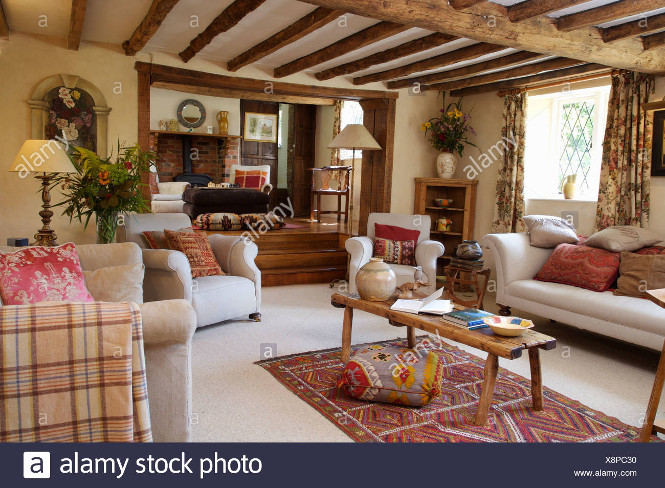 White Sofas And Armchairs With Rustic Wooden Coffee Table In Beamed Cottage Sitting Room With White Carpet Kelim Rug Stock Photo Alamy