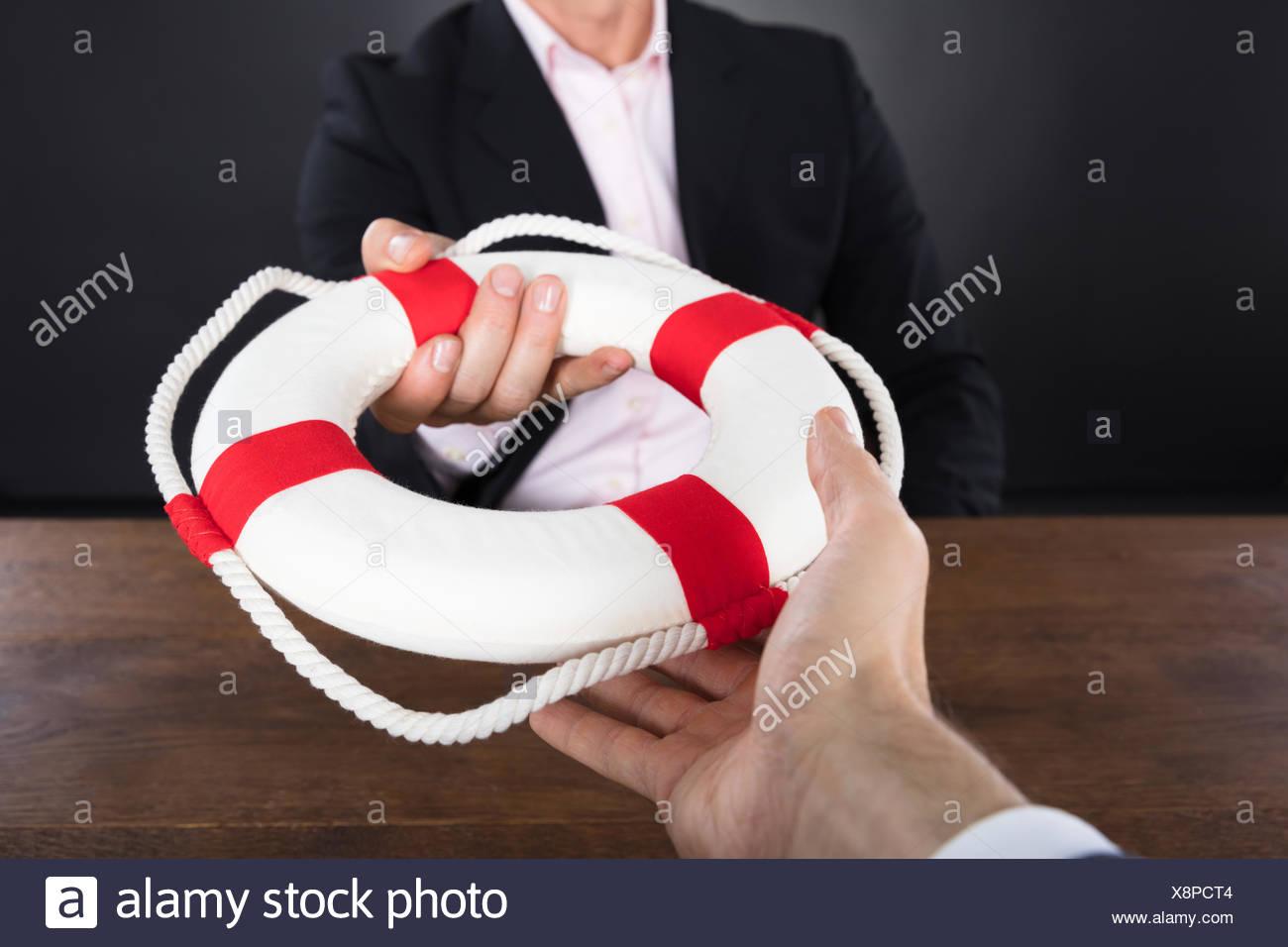 Businessman Passing A Lifebuoy To A Partner - Stock Image