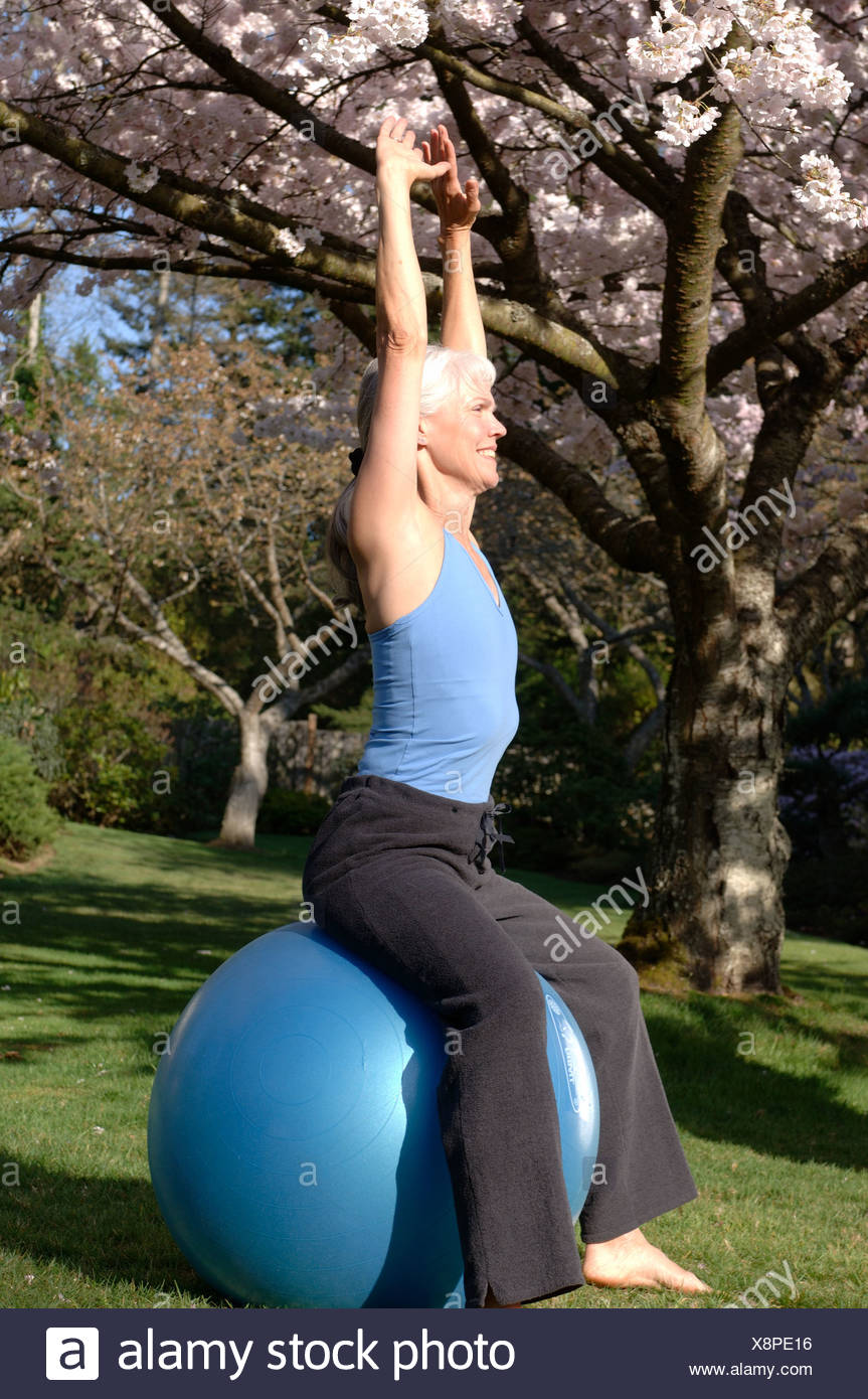 Mature woman stretching on exercise ball outdoors - Stock Image