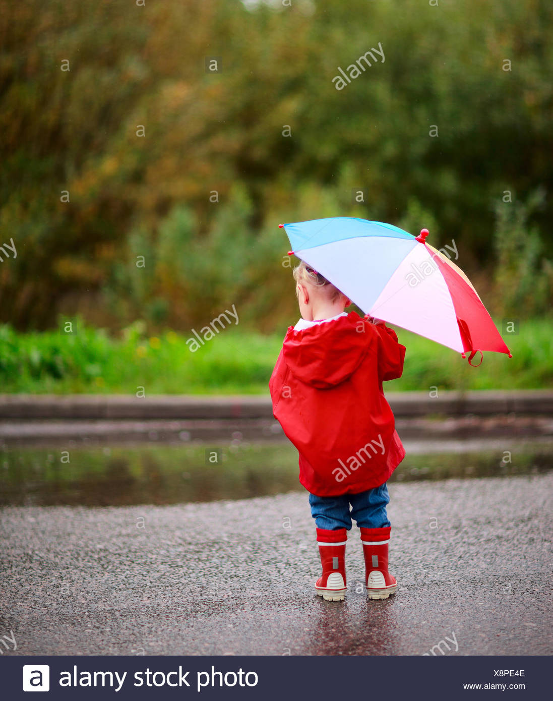 view from behind a little girl with an umbrella - Stock Image