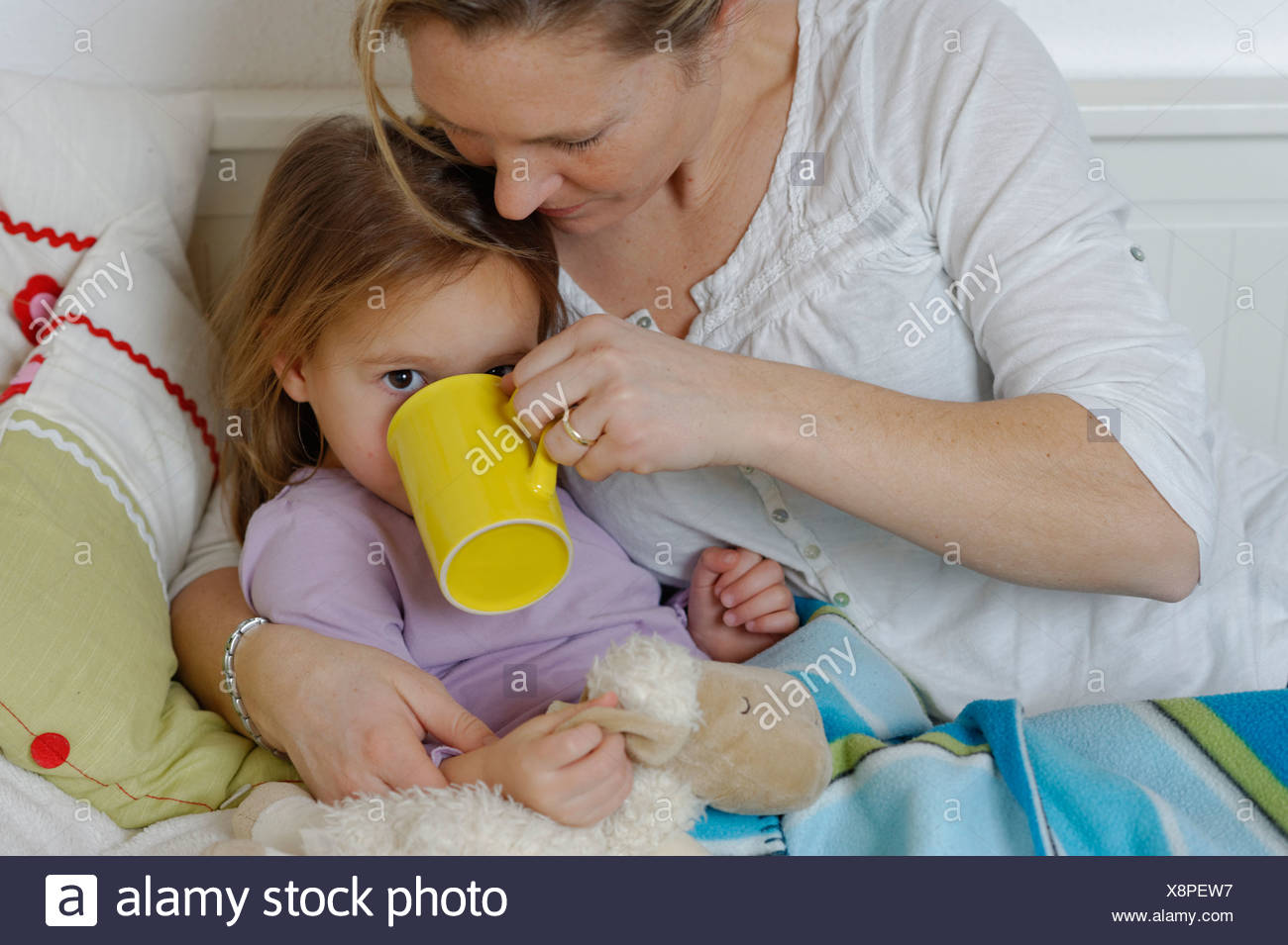 Mother taking care of her sick daughter, dispensing hot tea, girl lying in bed - Stock Image
