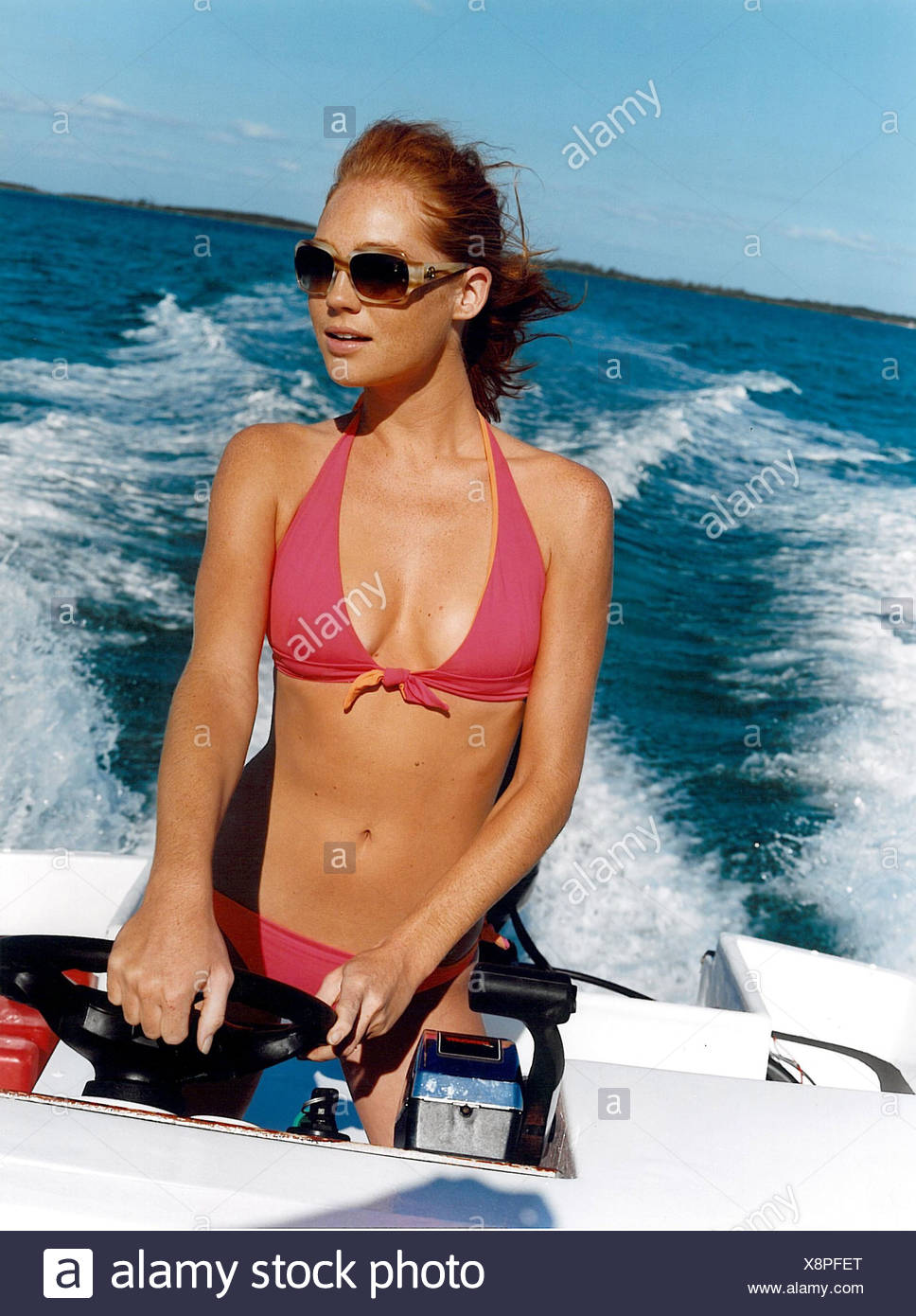 Female wearing a pink bikini and sunglasses with red hair tied back in a  pony tail driving a motboat Frowein