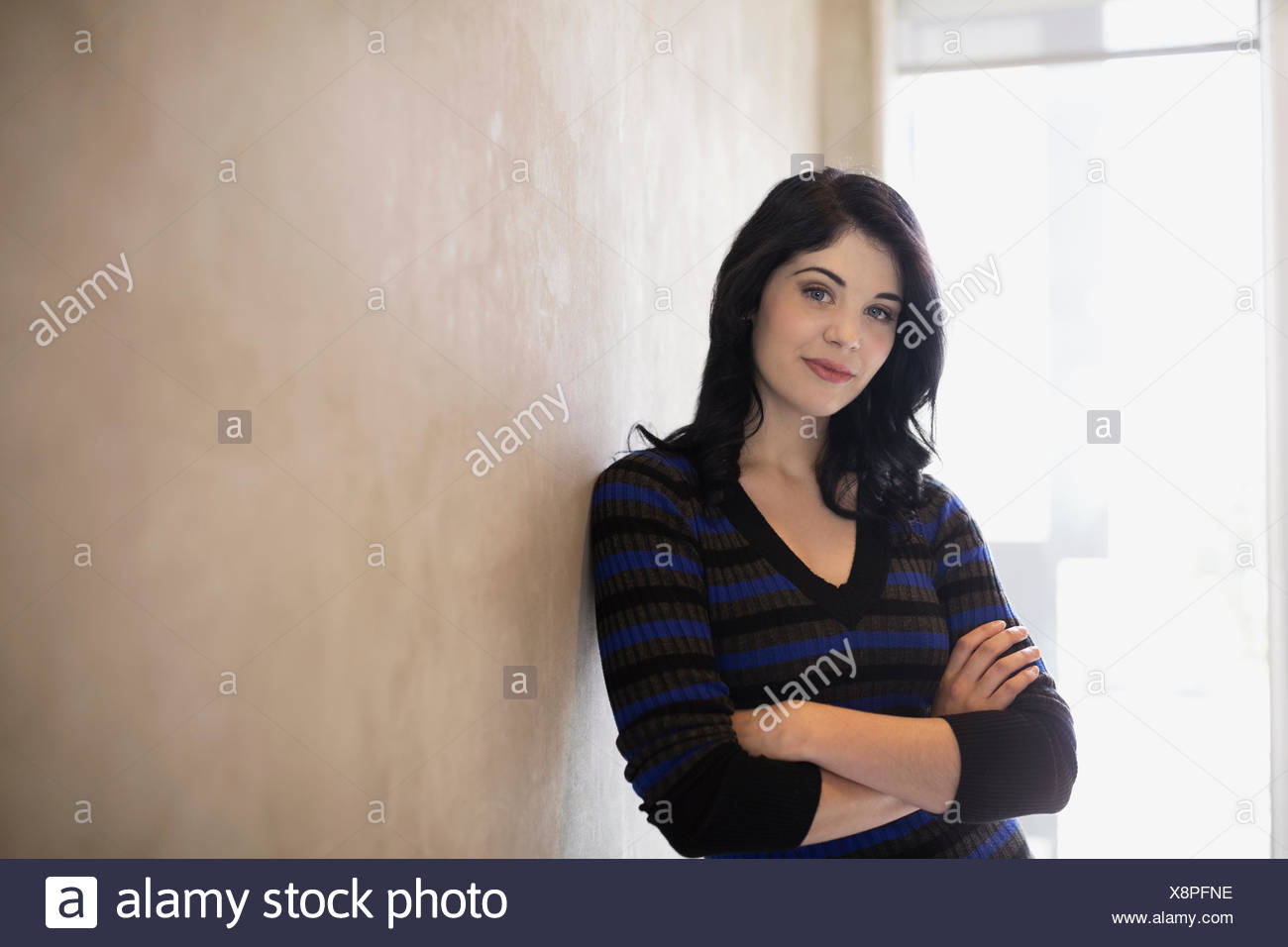 Portrait confident woman with arms crossed leaning wall - Stock Image