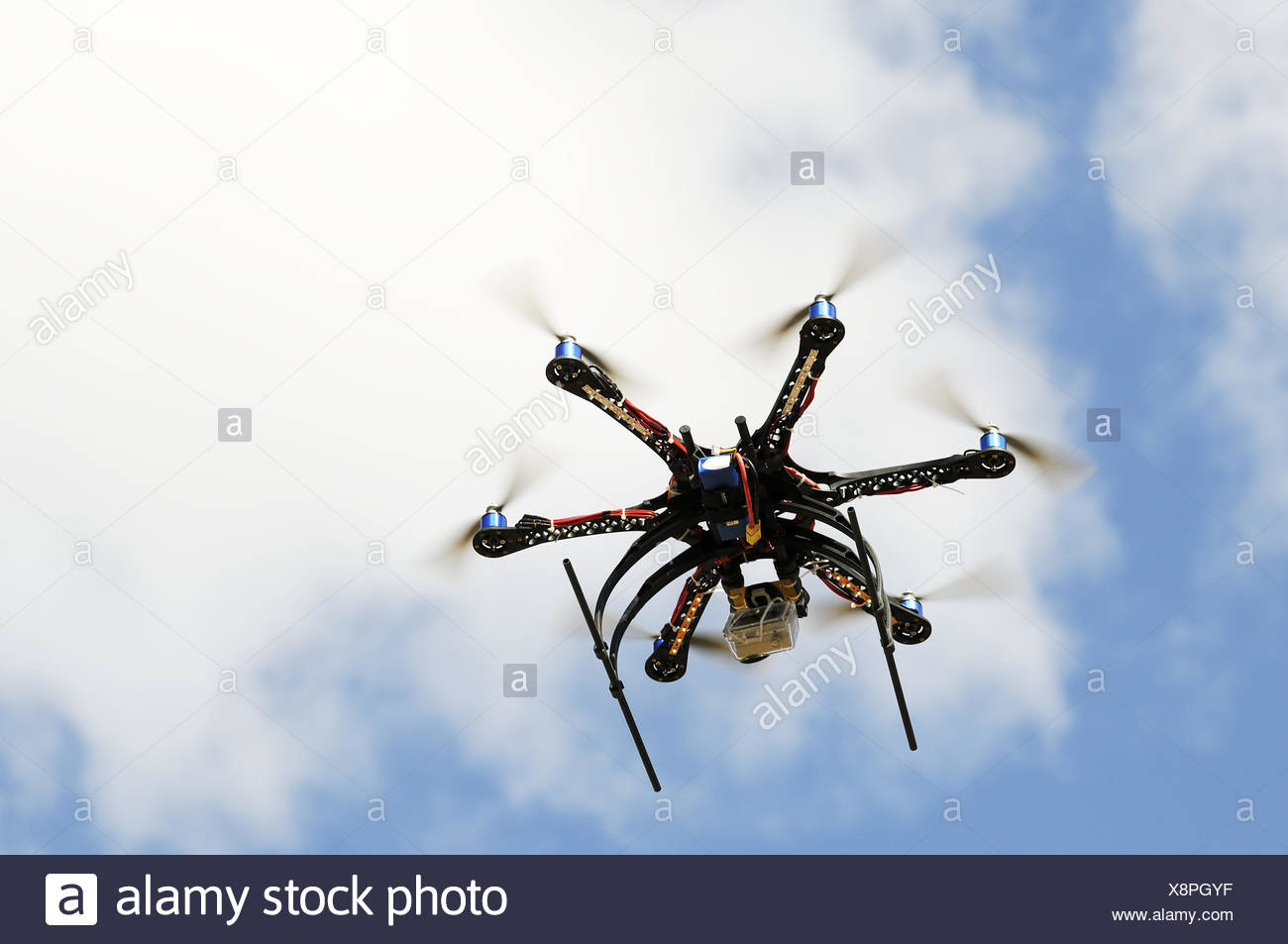 Hexacopter aircraft model in flight over blue sky - Stock Image