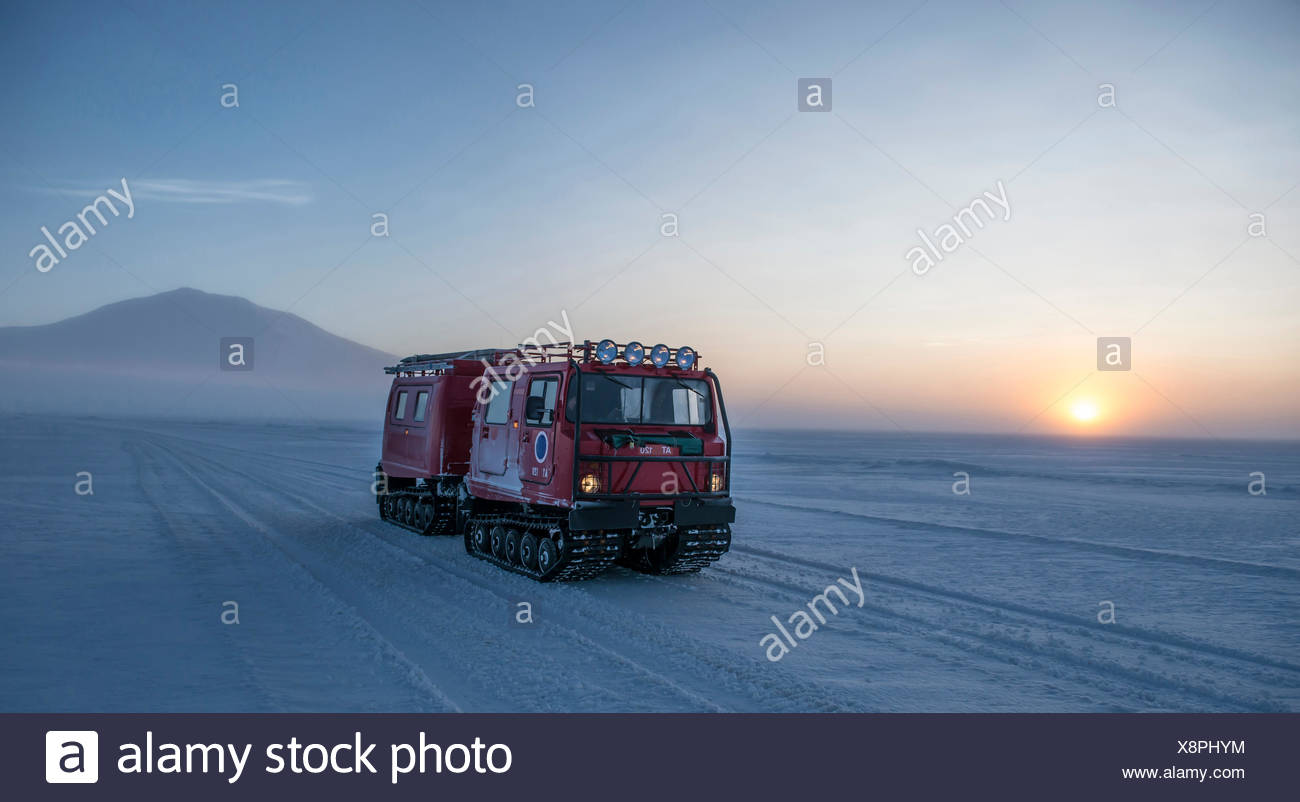 A vehical travels across the sea ice at the sun rises over McMurdo Sound in the Ross Sea, Antarctica. - Stock Image