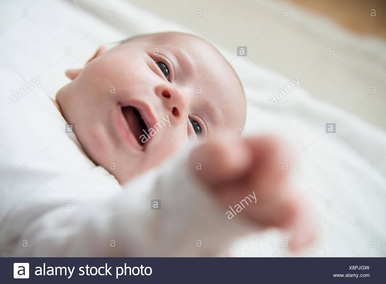 Baby boy lying on bed with mouth open - Stock Image