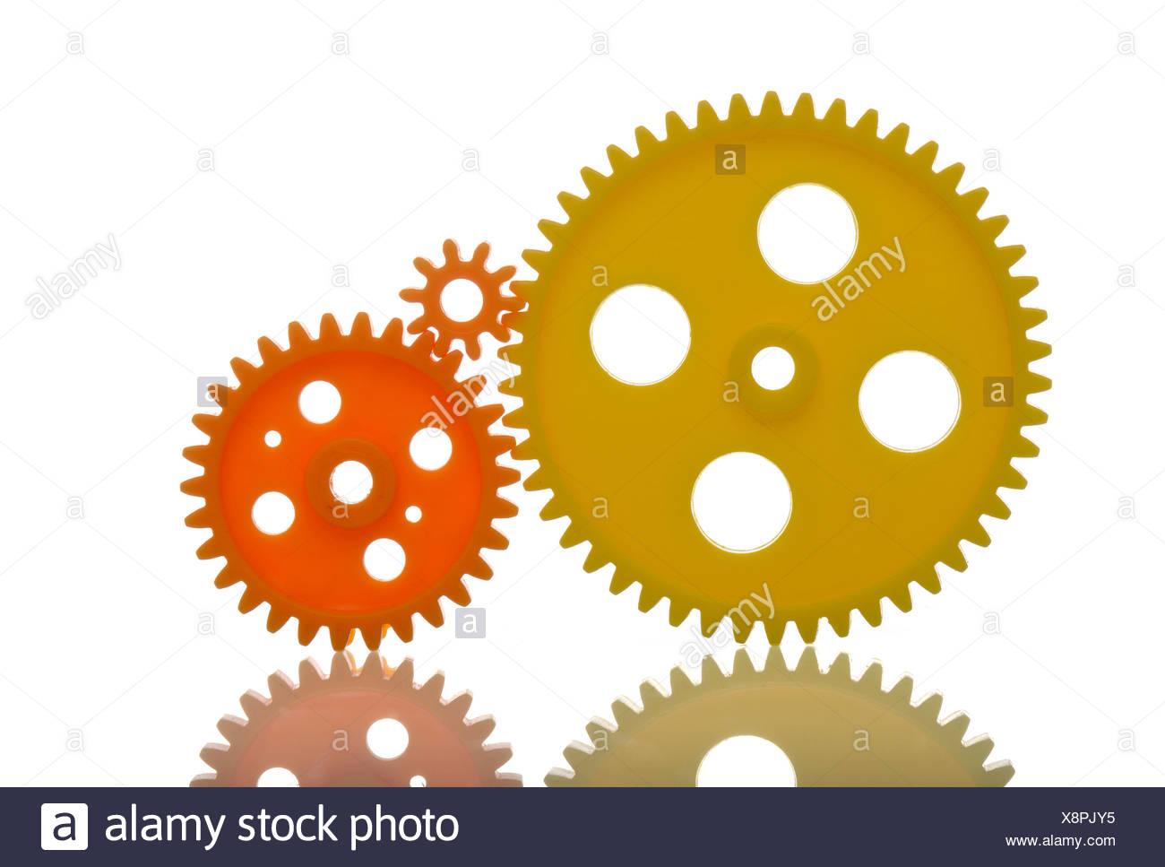 Yellow and orange cog wheels, symbolic image - Stock Image