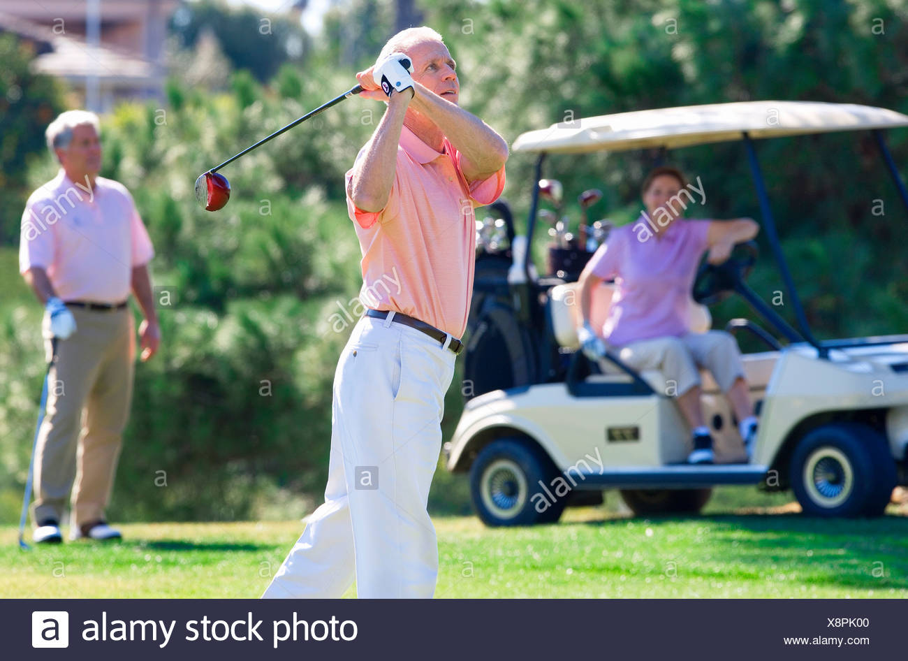 Three mature adults playing golf, mature man in polo shirt driving golf ball from tee, mature couple watching from golf buggy - Stock Image