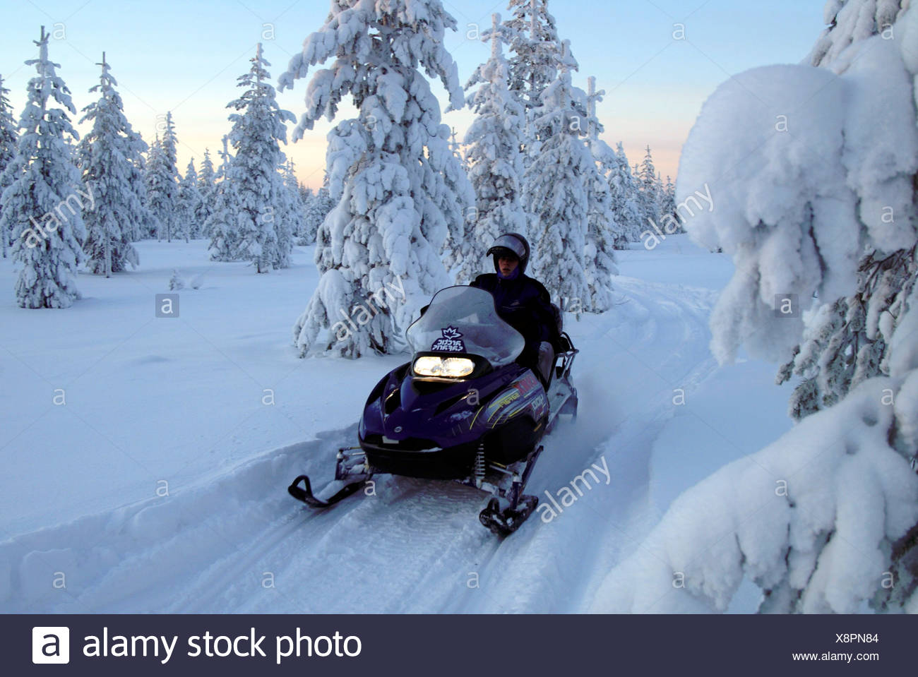 Finland tourists on snowmobile - Stock Image