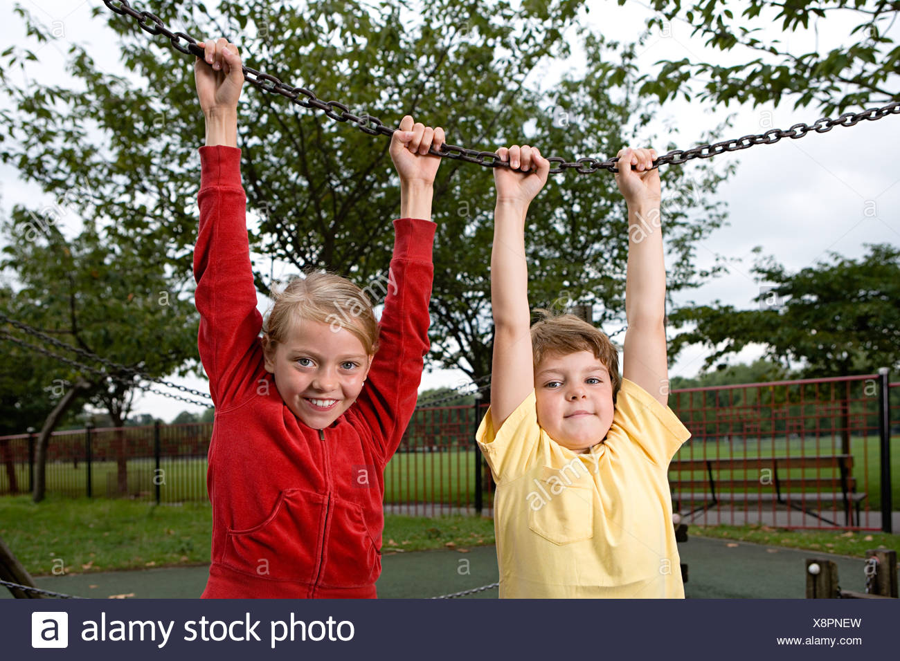Boy and girl holding a chain - Stock Image