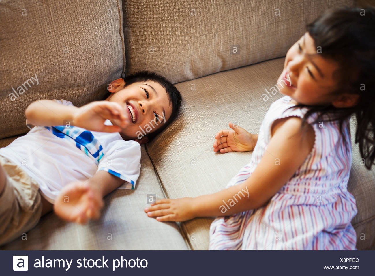 Family home. Two children playing on the floor, giggling. - Stock Image