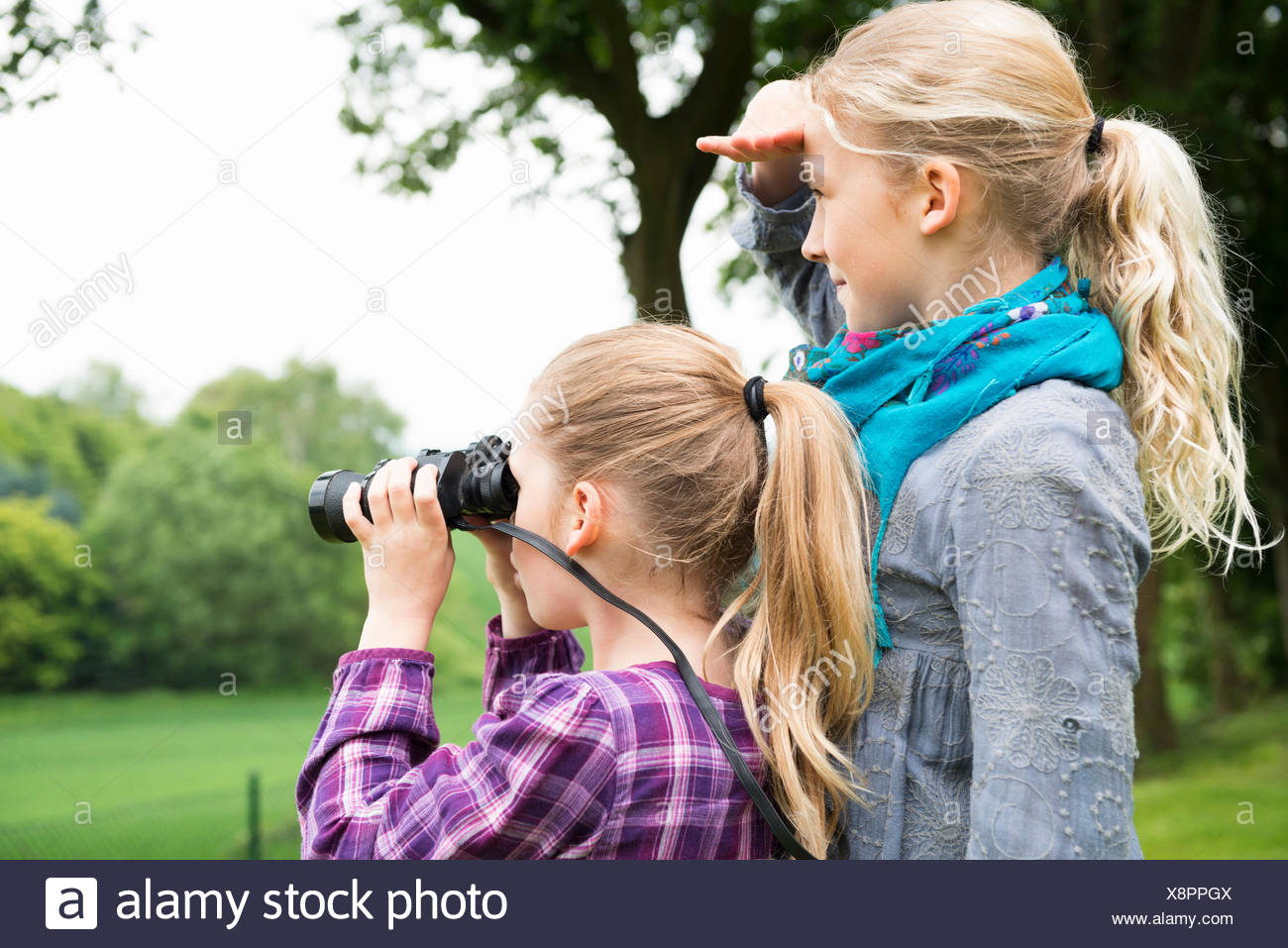 Two sisters using binoculars - Stock Image