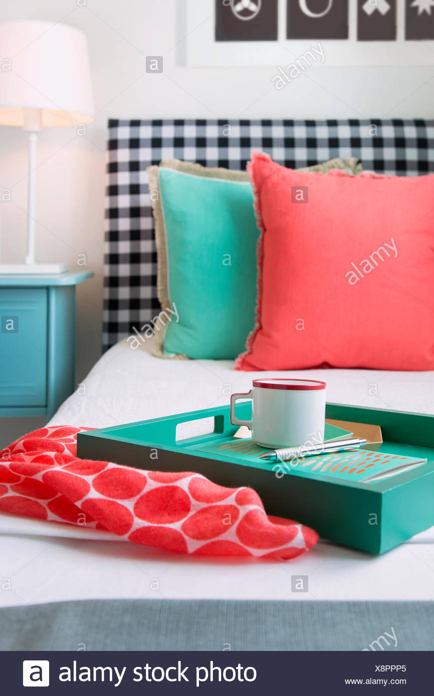 Coral and seafoam green decor on bed - Stock Image