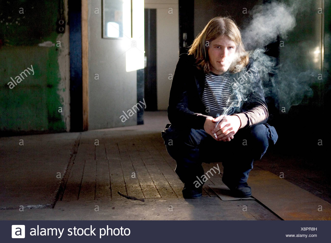 Young man smoking a cigarette in an empty warehouse, Zurich, Switzerland. - Stock Image