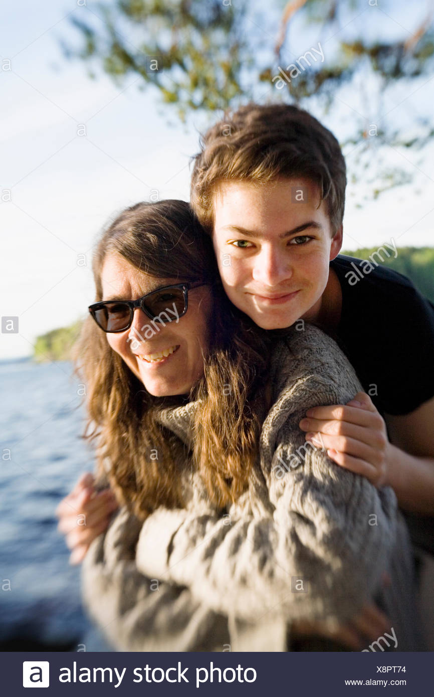Sweden, Dalarna, Portrait of teenage boy (14-15) with his mom on lakeshore - Stock Image
