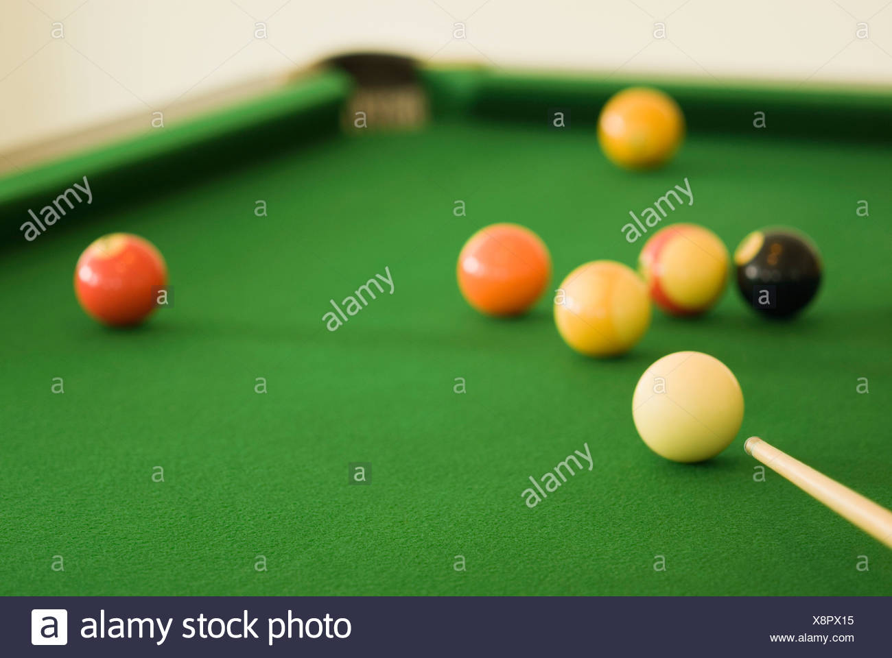 Close-up of a pool cue with pool balls on a pool table - Stock Image