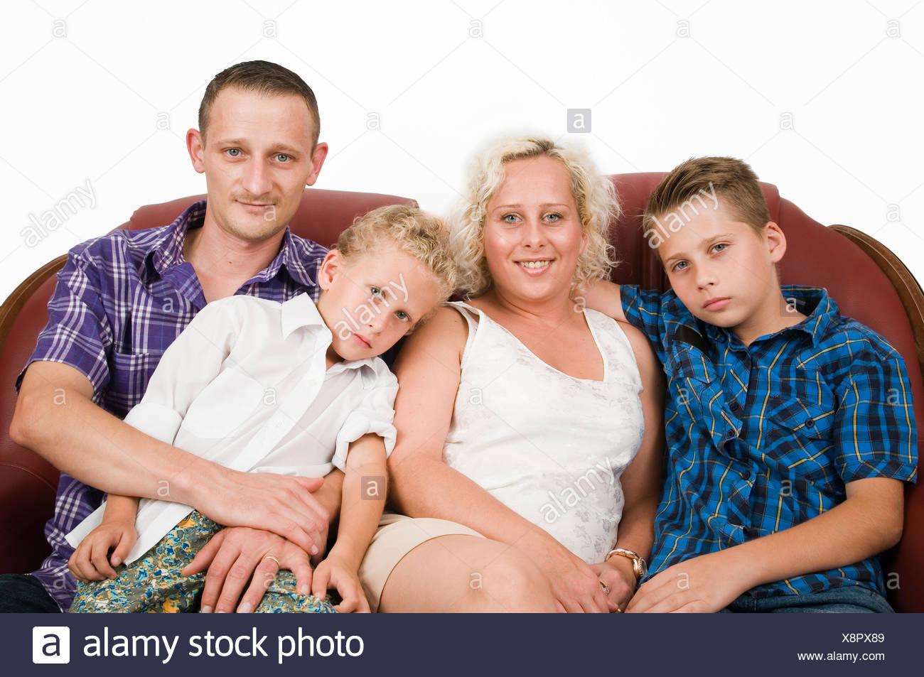 Oberkörper-Porträts zweier Eltern mit ihren zwei Söhnen im Alter von 7 und 13 Jahren auf einem braunen Leder-Sofa vor weisser Wand - Stock Image