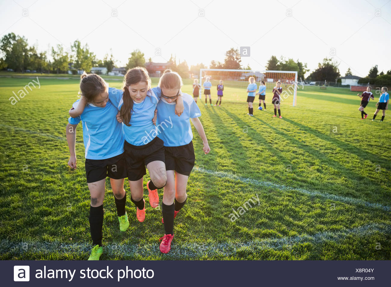 Middle school girl soccer players helping injured teammate off field - Stock Image