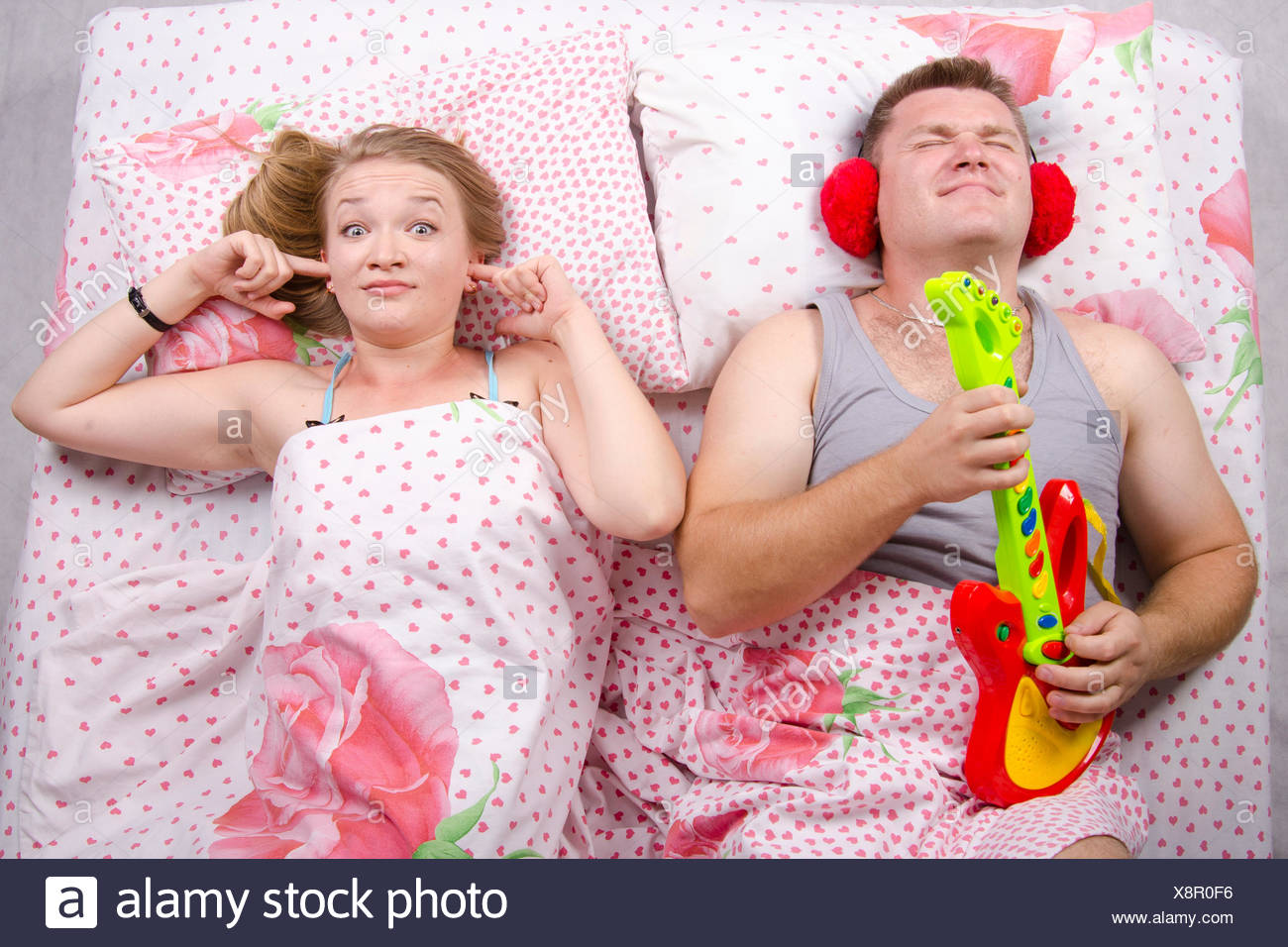 Young couple lying in bed  Husband plays guitar and shouts