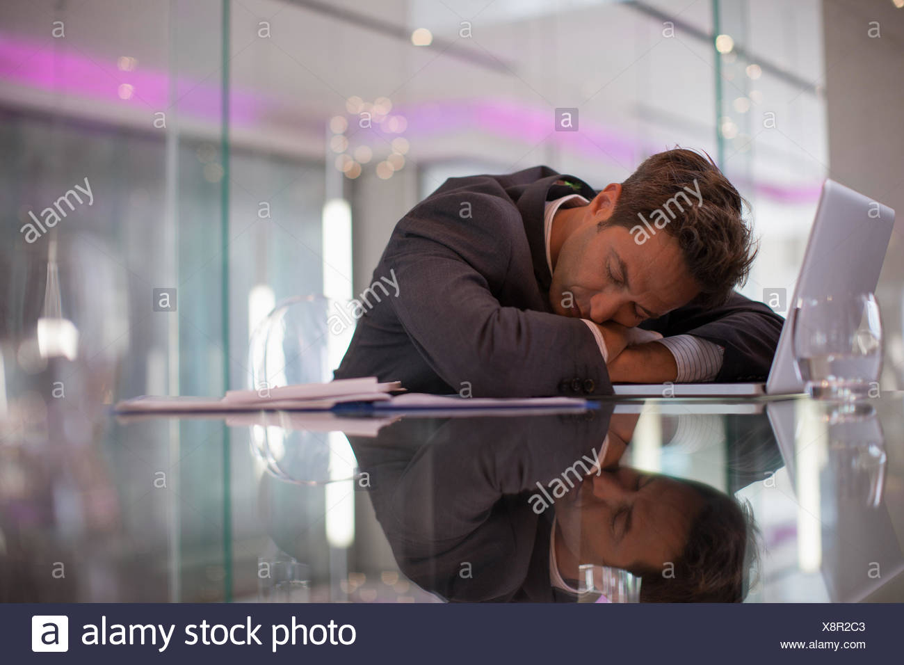 Businessman sleeping at desk in office - Stock Image
