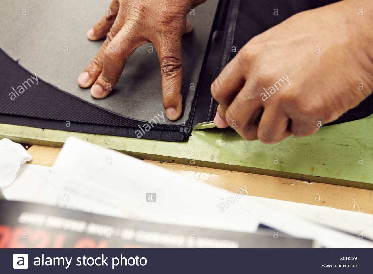 Close up of hands cutting leather - Stock Image