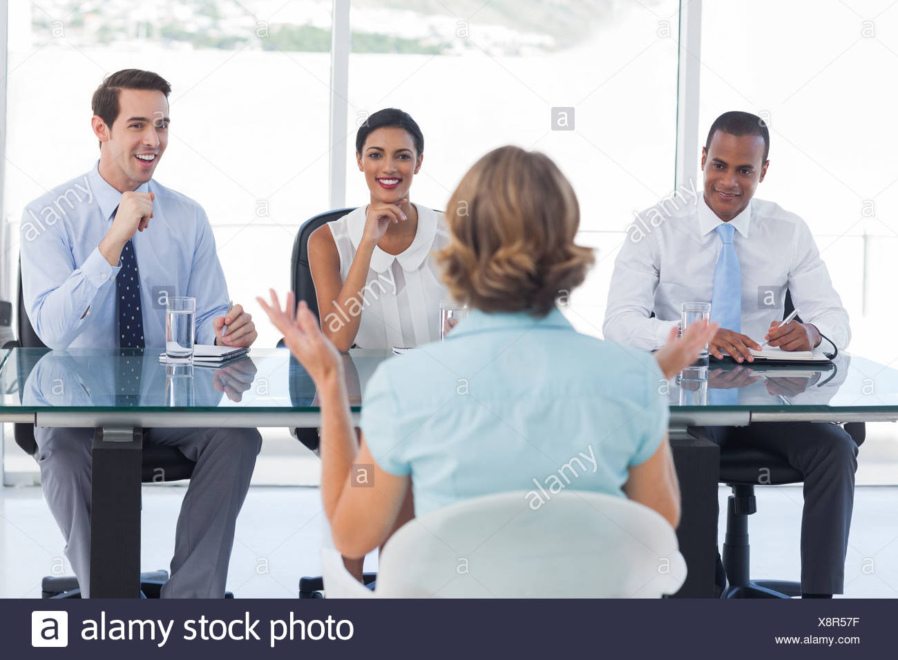 Recruitment consultants smiling in front of an applicant - Stock Image