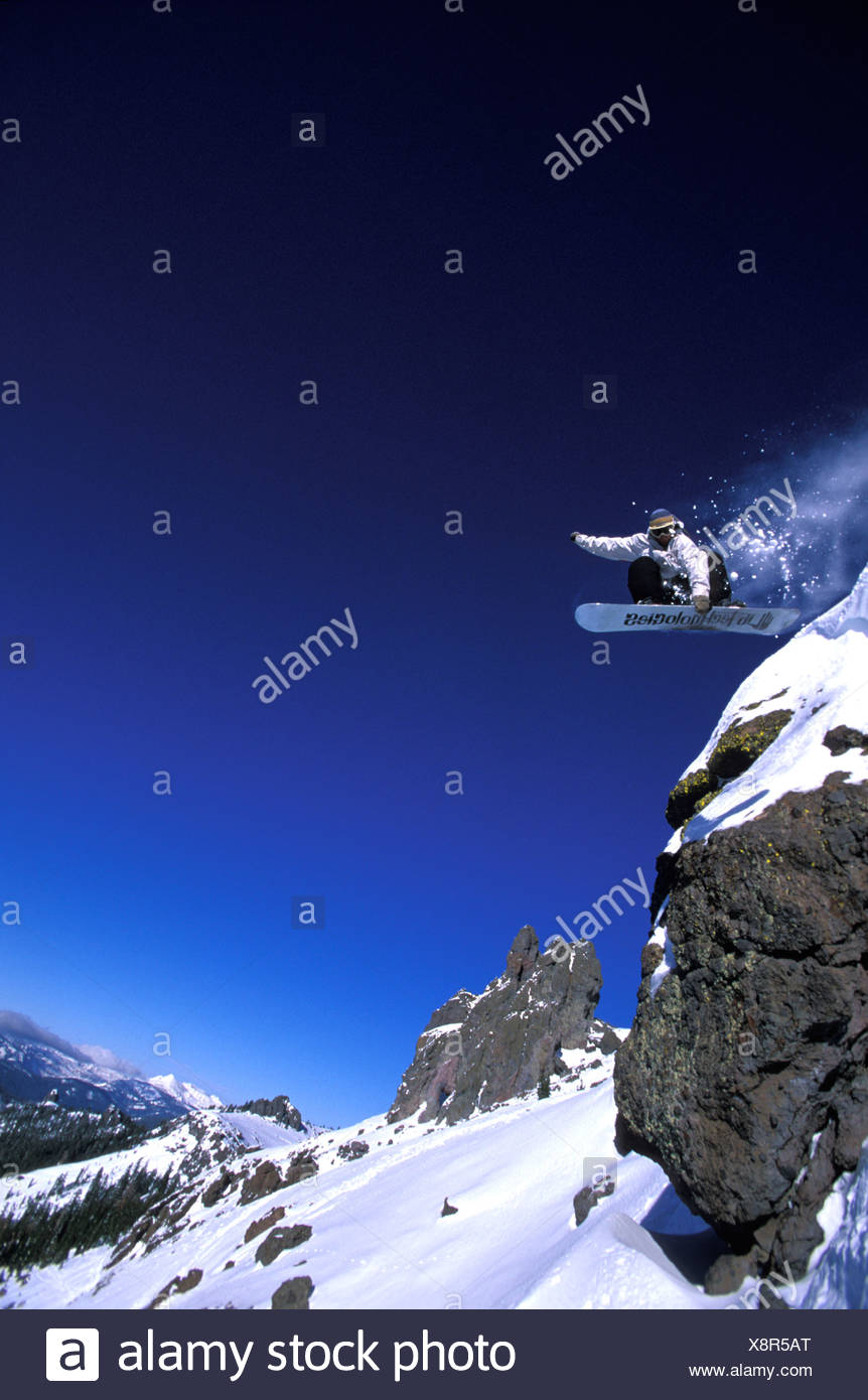 A snowboarder launching off a cliff and grabbing his board near Lake Tahoe, California. - Stock Image