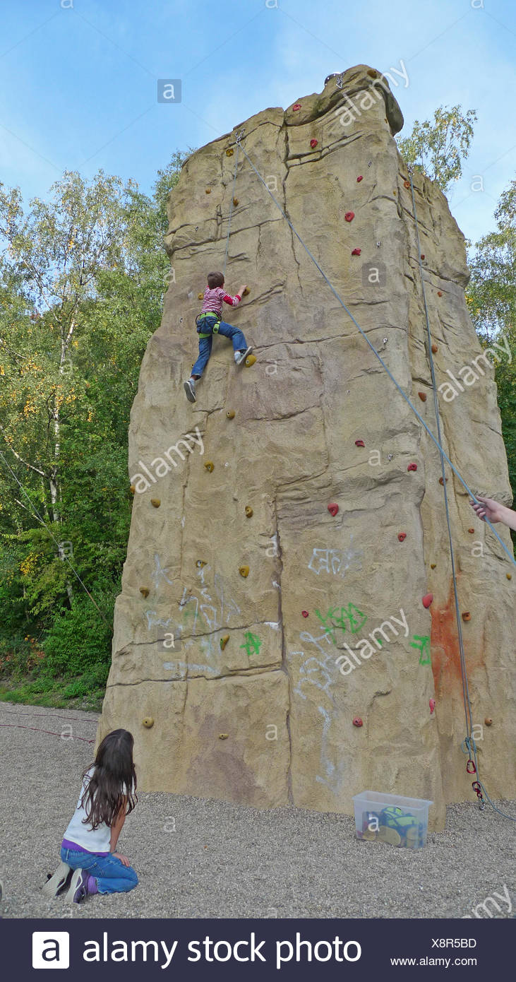 little boy climbing roped up in a professional climbing wall being watched by a girl Stock Photo