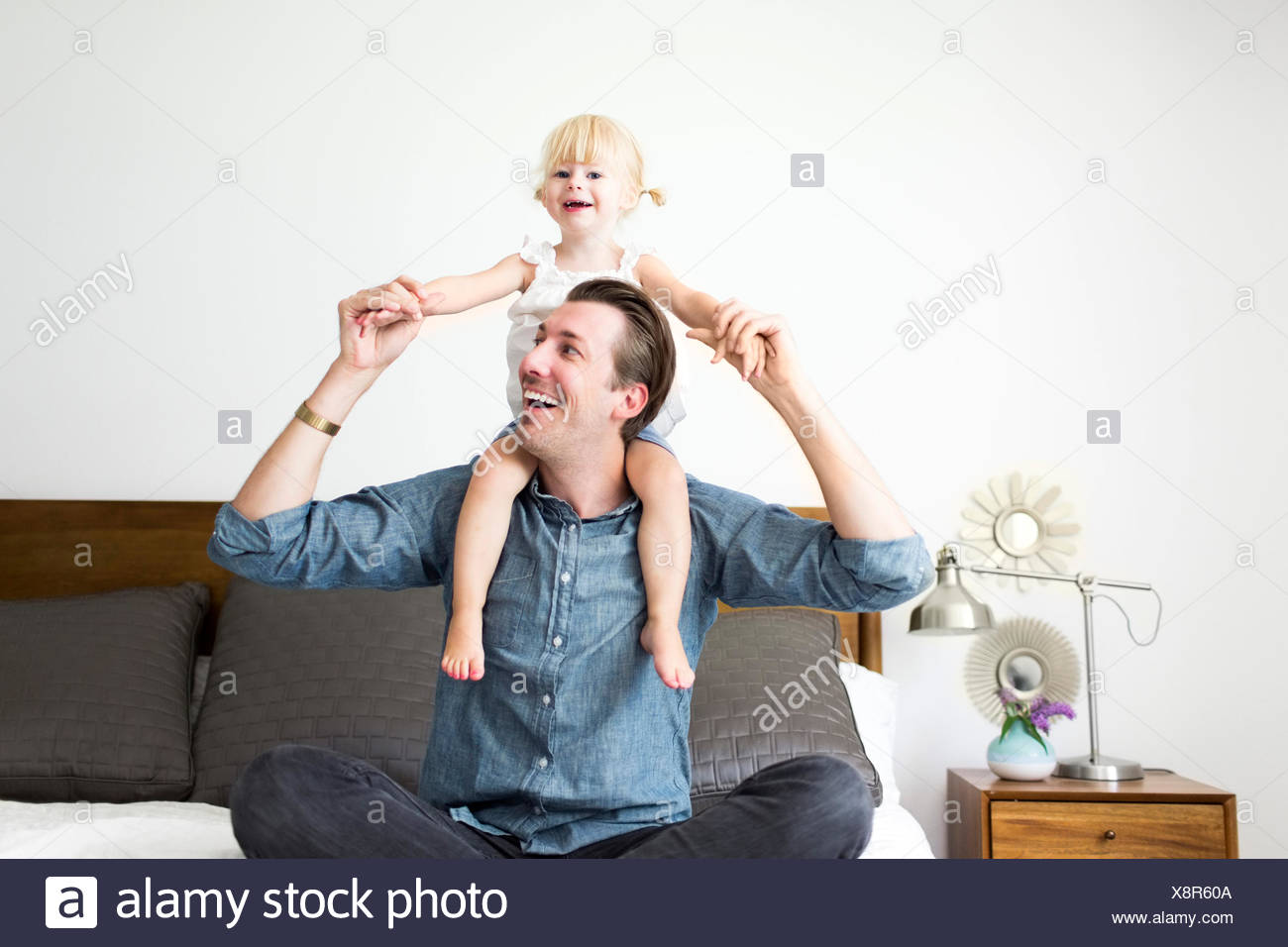 Portrait of father carrying daughter (2-3) on shoulders - Stock Image