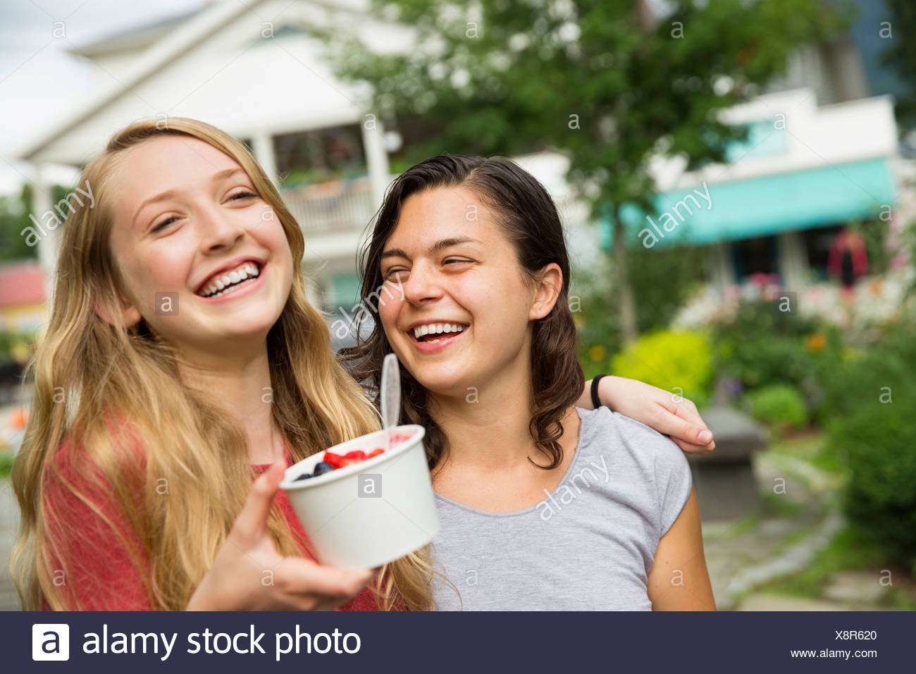 Two girls hugging and laughing. - Stock Image