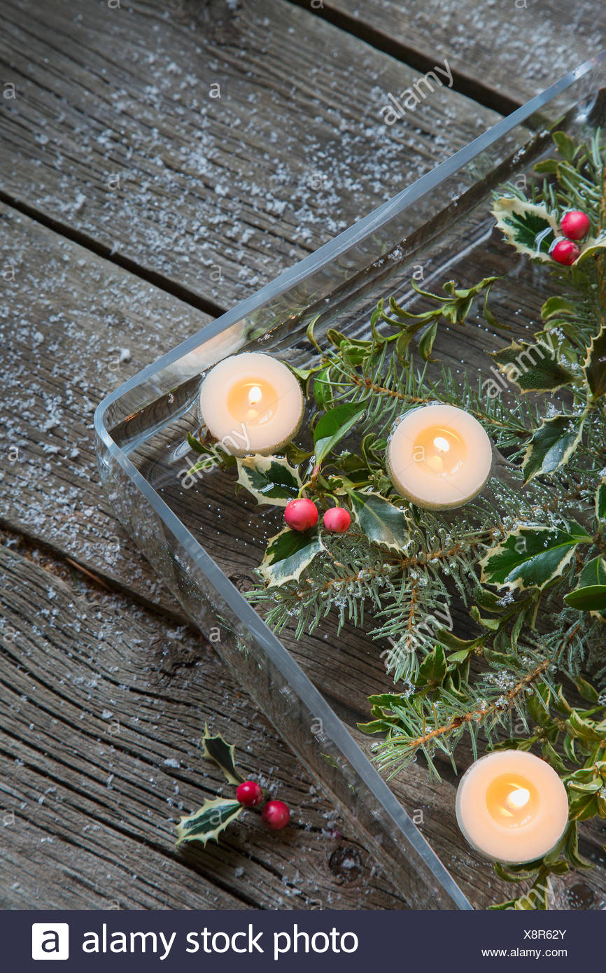 Christmas Floating Candles.Floating Candles And Christmas Holly In Square Vase Stock