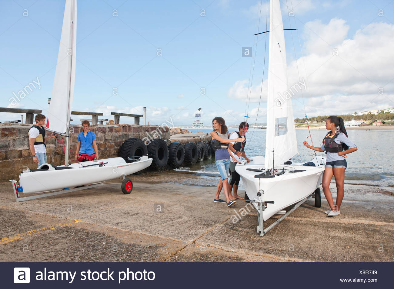 Young adult friends preparing sailboats on waterfront - Stock Image