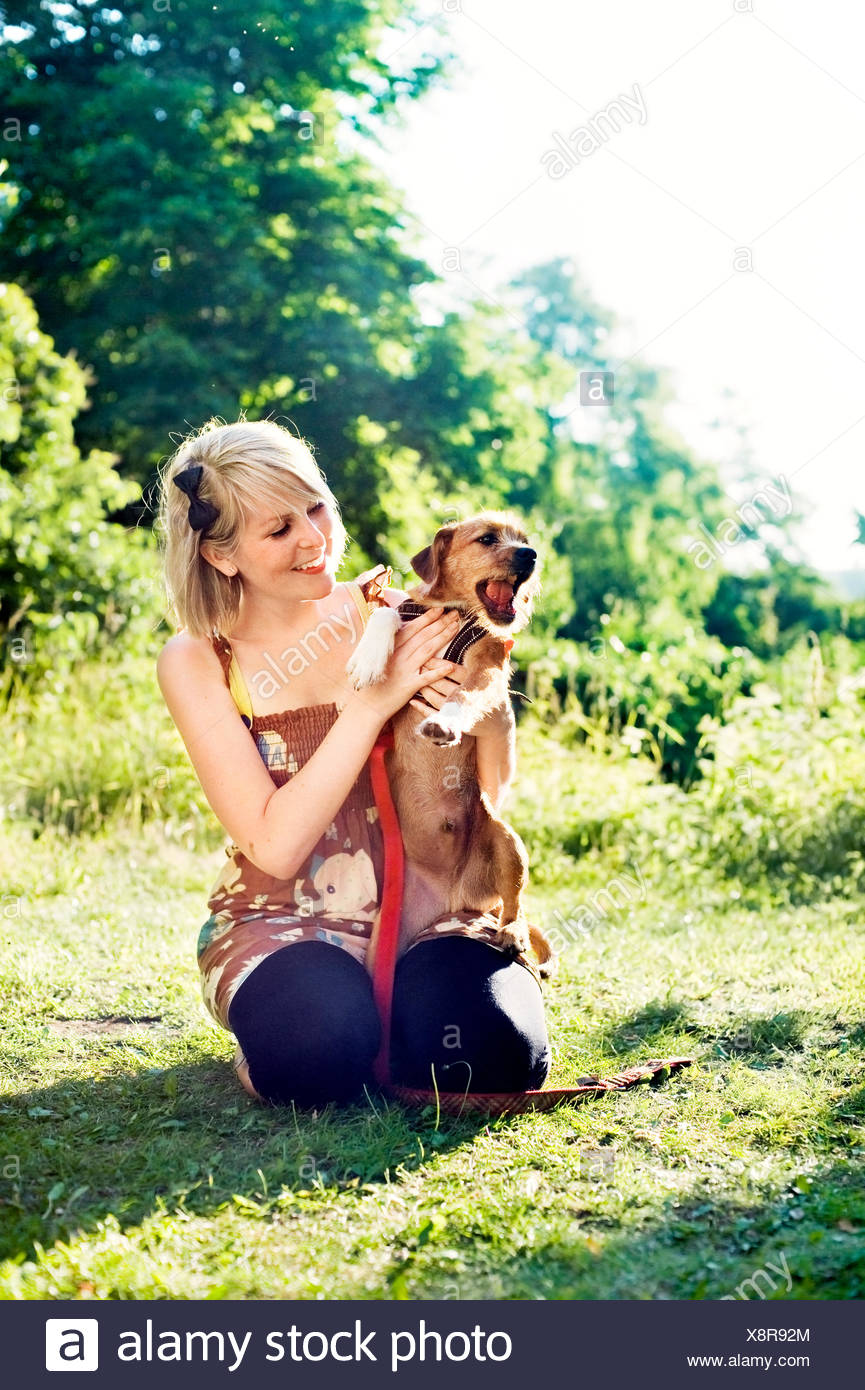 Sweden, Uppland, Danderyd, Young woman sitting on grass with terrier - Stock Image