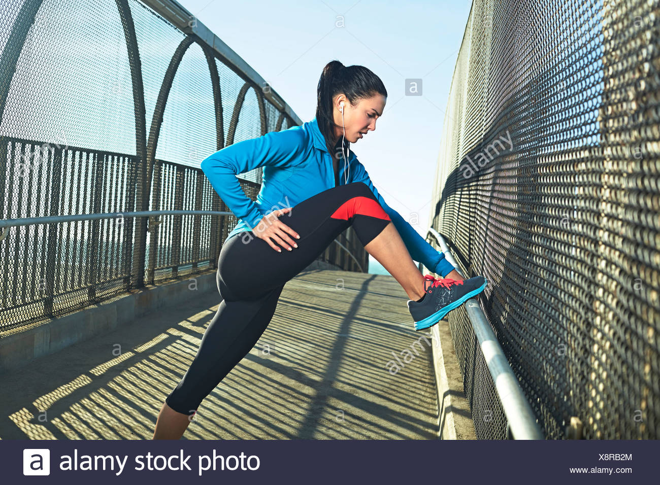Mid adult woman stretching on bridge - Stock Image
