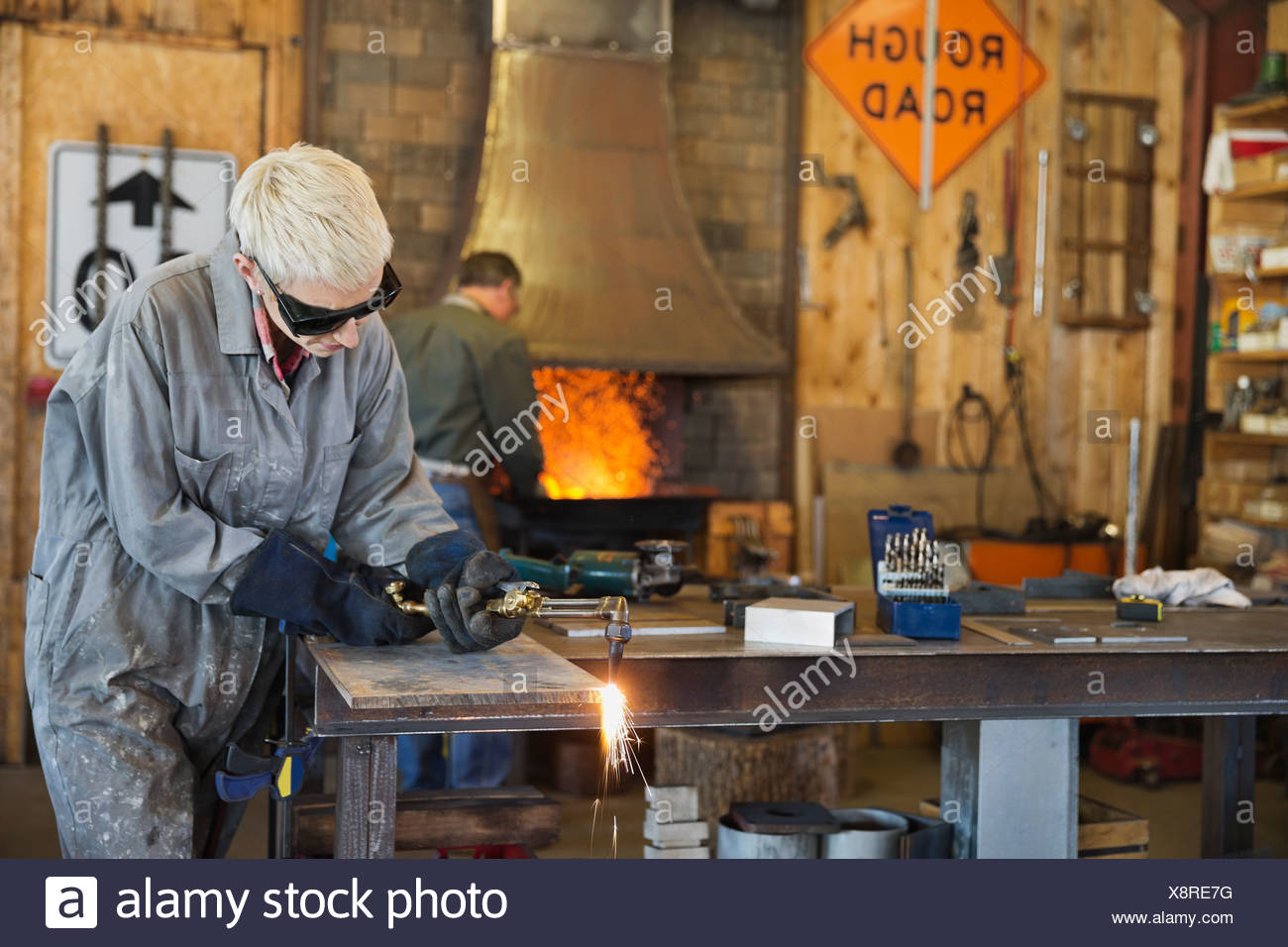 Female welder cutting metal with torch - Stock Image