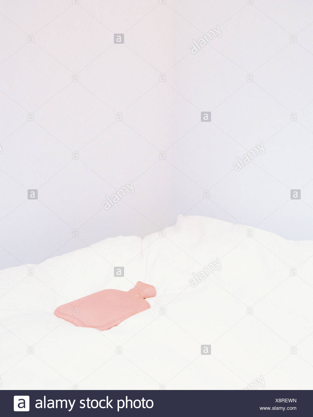 A hot-water bottle on a white bed. - Stock Image