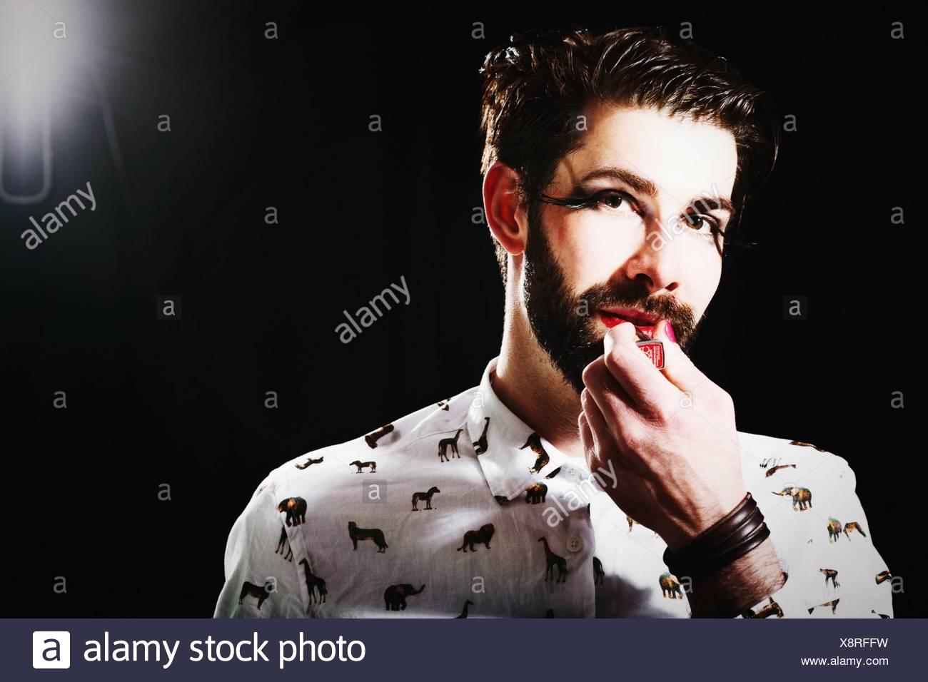 Portrait Of Man Applying Lipstick Standing Against Black Background - Stock Image