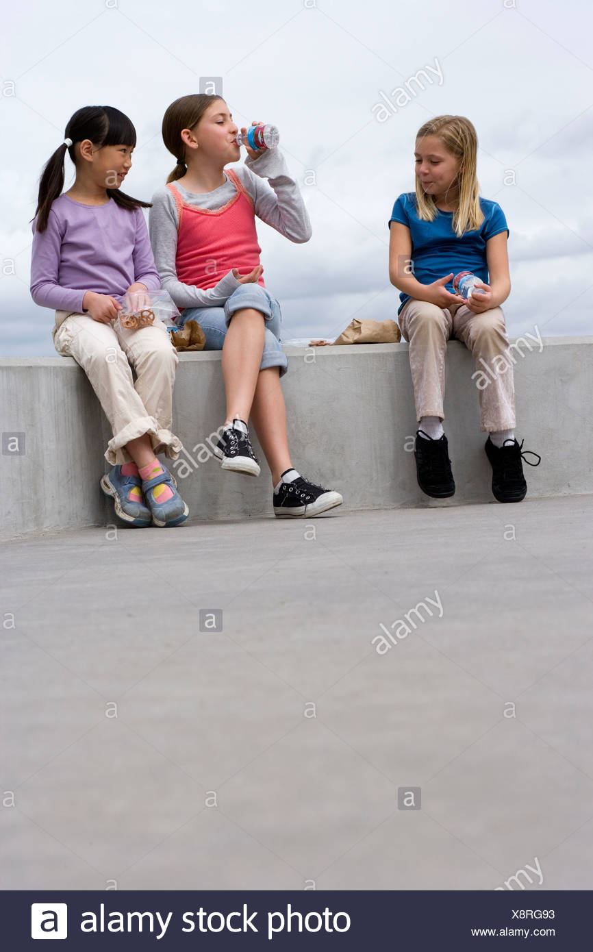 Three girls 9 11 sitting on wall eating packed lunch one girl drinking from bottle - Stock Image