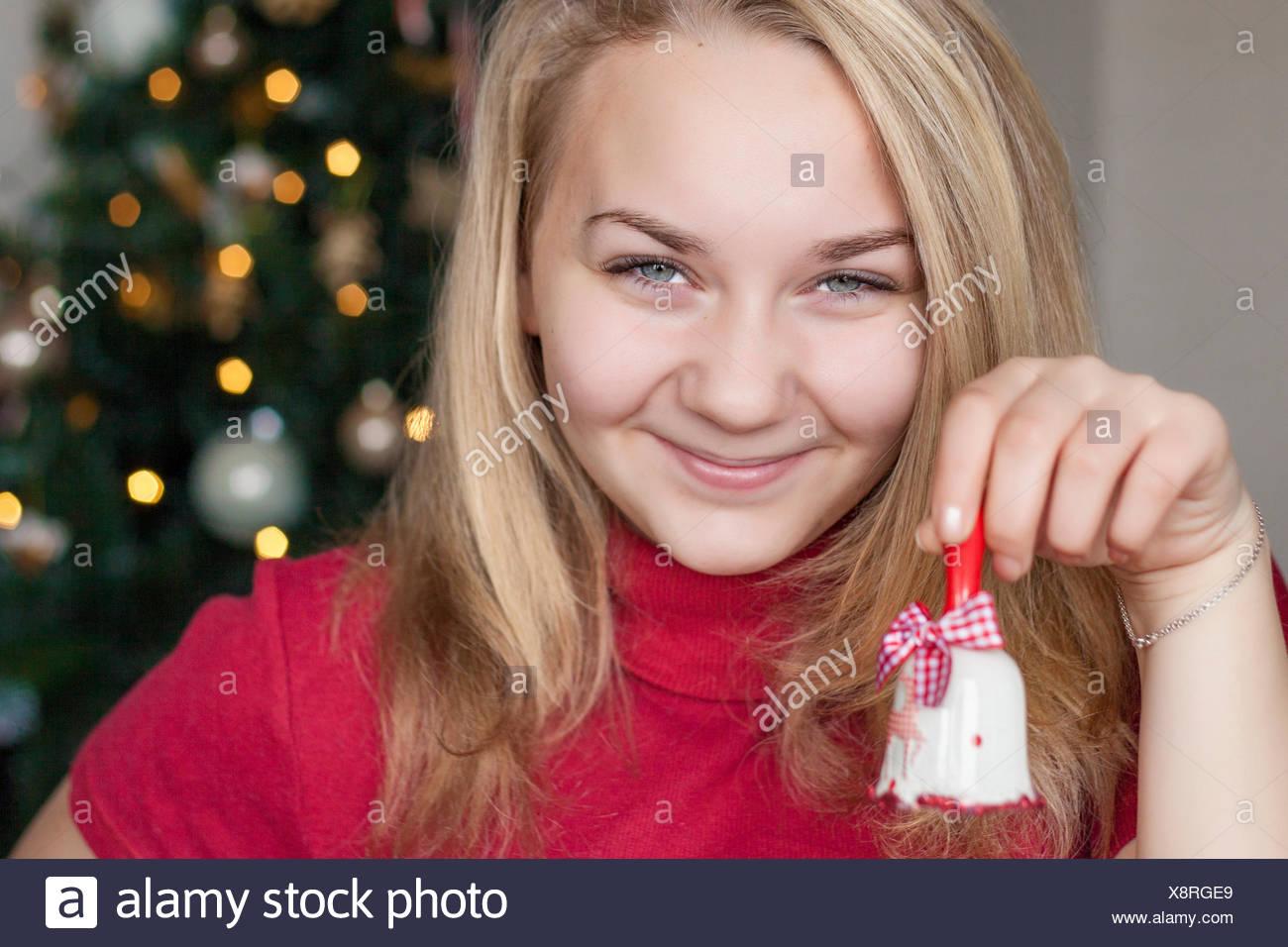 Smiling girl (14-15) holding christmas bell - Stock Image