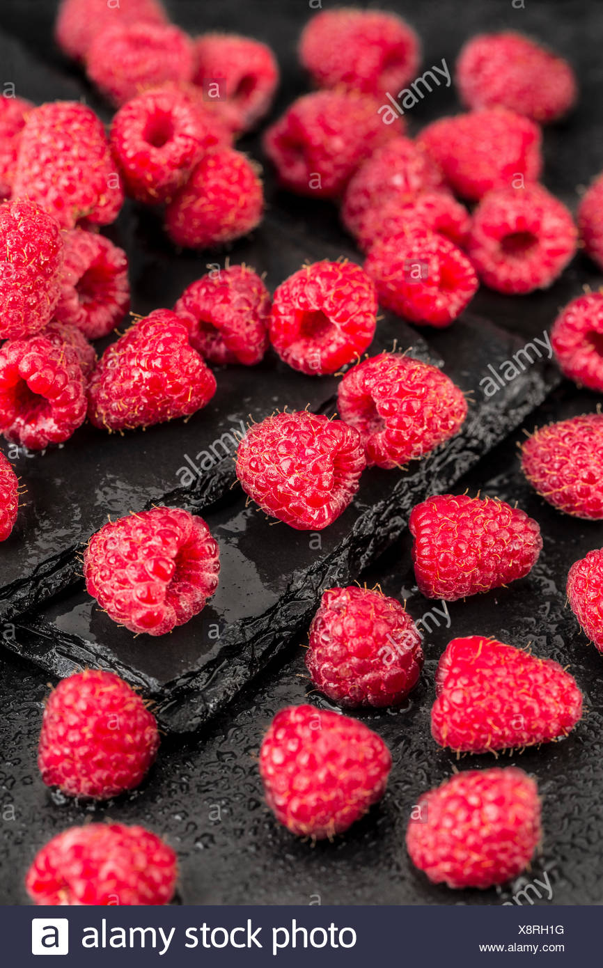 Wet red raspberries on a black slate background - Stock Image