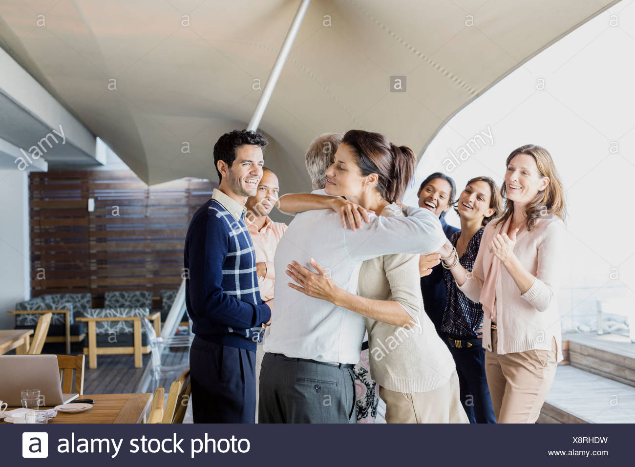 Business people hugging in office - Stock Image