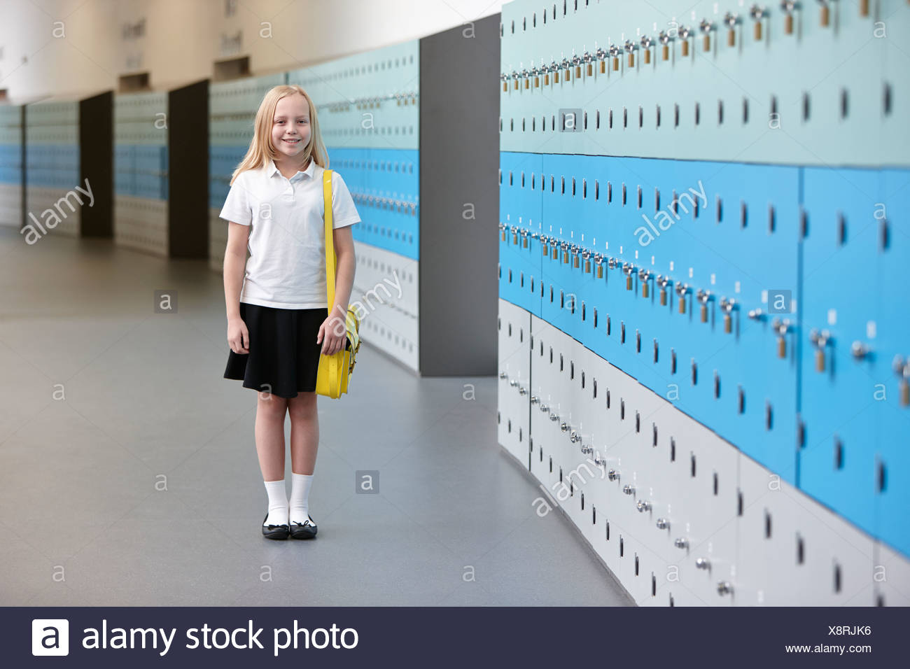 Portrait of schoolgirl in corridor - Stock Image