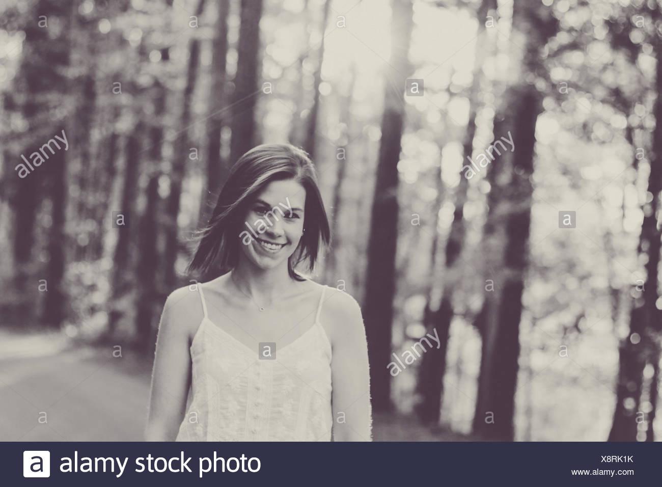 Woman walking down road during springtime - Stock Image