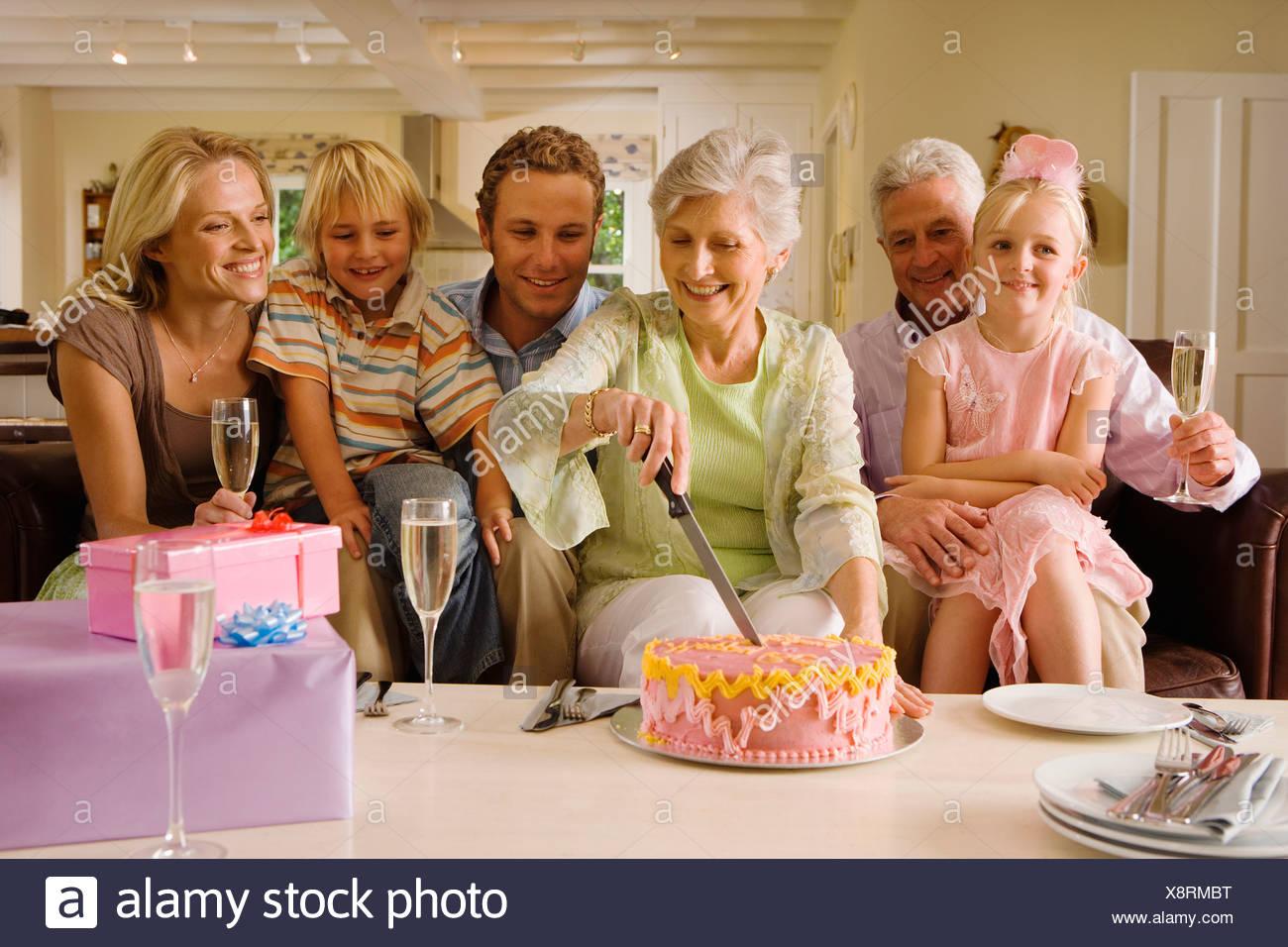 mature woman cutting birthday cake stock photos & mature woman