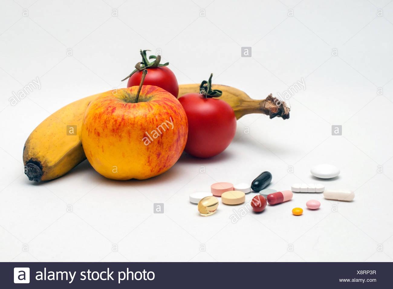 verschiedene bunte Tabletten, Apfel, Banane und Tomaten, isoliert Stock Photo
